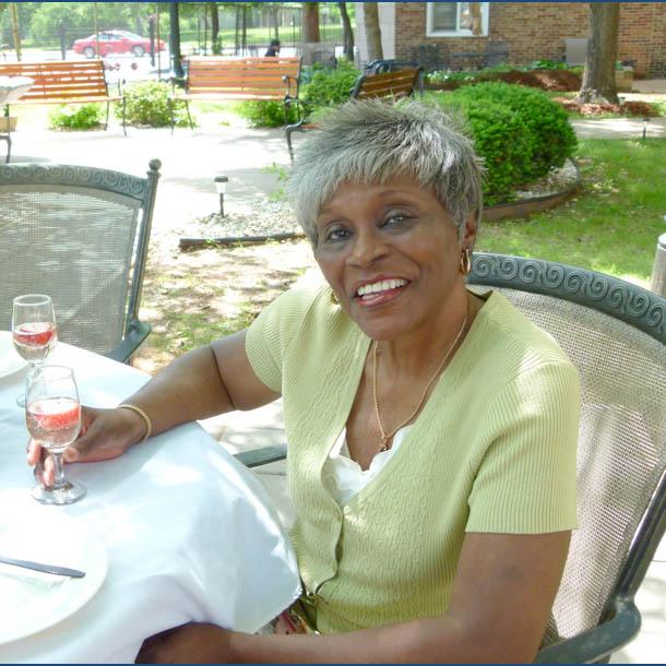 Woman enjoying patio at Tower Grove community